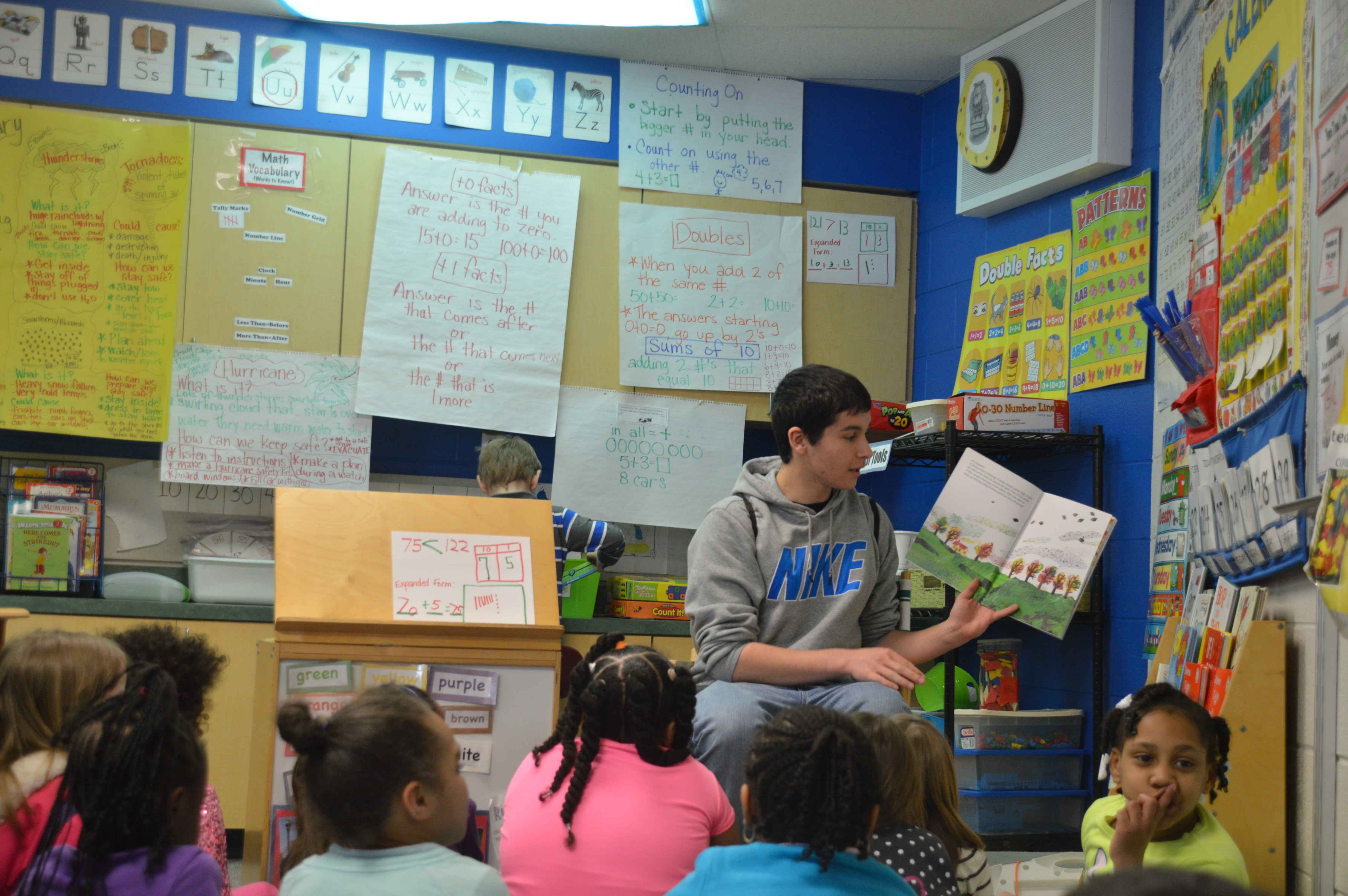 Andy Butkovitch '16 reads to students in the classroom.