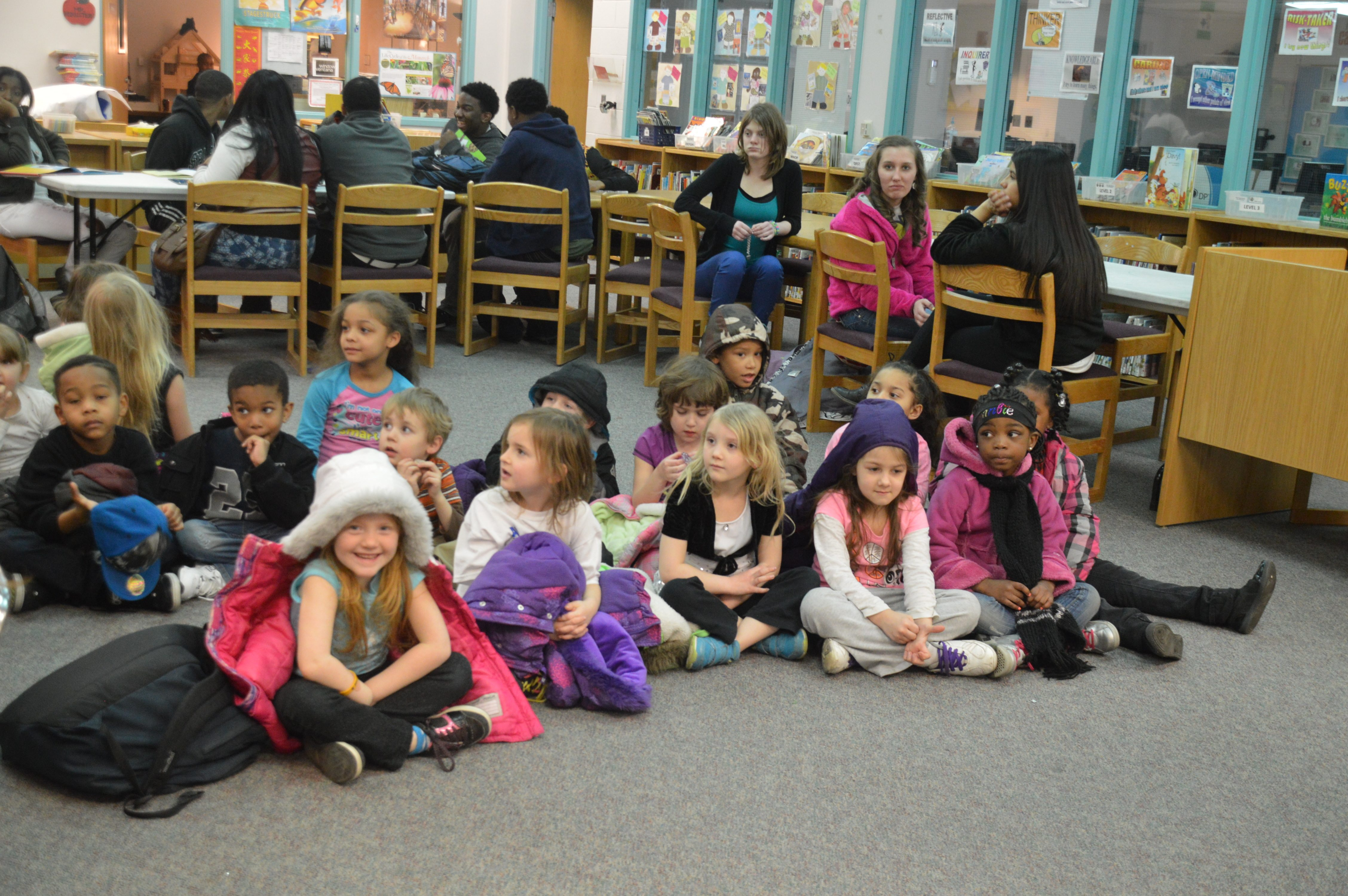Excited elementary students are led into the library while they wait for high schoolers to begin story time.