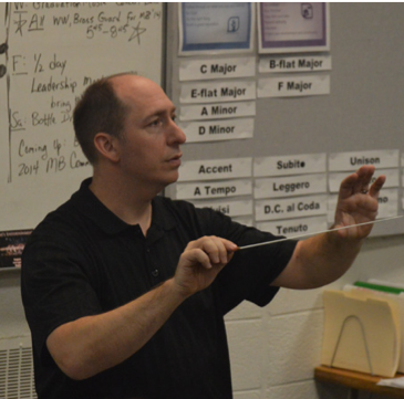Cross instructs band students on how to improve their rendition of Pomp and Circumstance