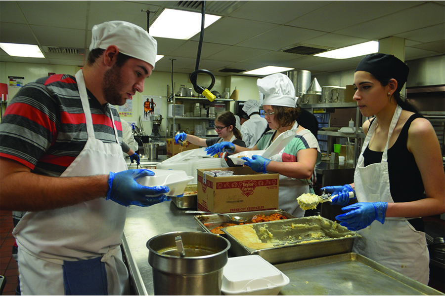 Clockwise; Dan Campbell '16, Emma Essler '17, Rebecca Albrecht '17 and Holly Salome '17 pack thanksgiving meals into take-out boxes for Detroit homeless.